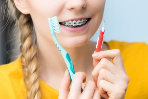 Young woman smiling cleaning and brushing teeth with braces using toothbrush